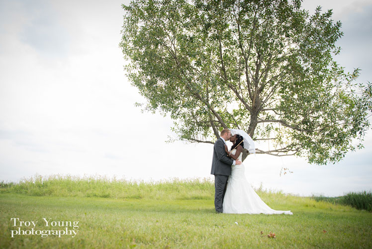 Bride-and-groom-kissing-under-a-tree-Calgary-wedding-planner1