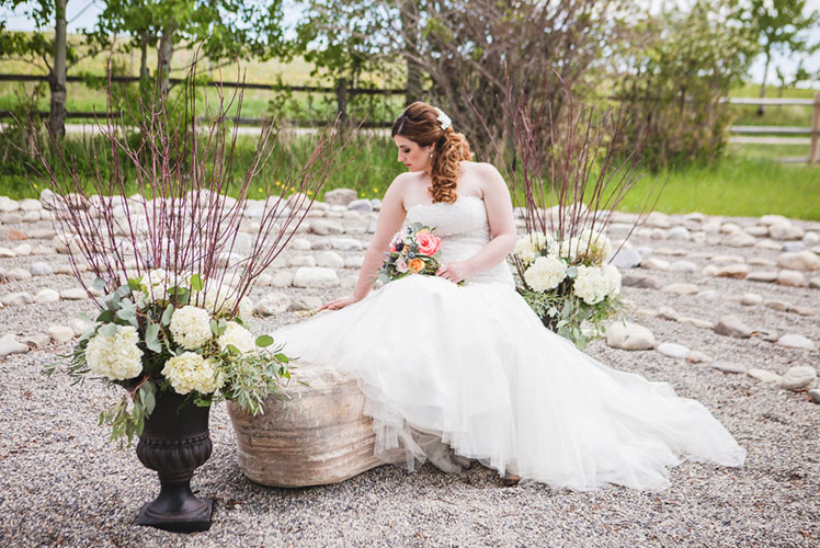 Bride-sitting-on-a-rock-surronded-by-flowers-Calgary-wedding-planner-1024x683