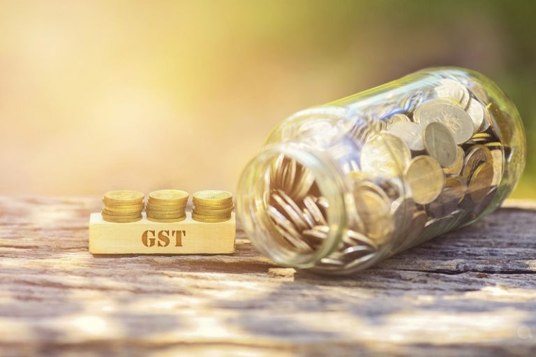 69265094 - gst word golden coin stacked with wooden bar on shallow dof green background